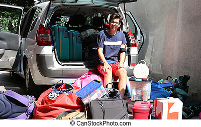 young teenager sitting on the car with a lot of luggage