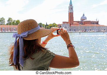 lady with a big straw hat taking a picture in the basin of...