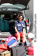 young boy loads the car with a lot of luggage before leaving for