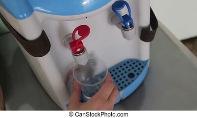Filling Cup At Water Cooler, Water Dispenser. Woman filling...