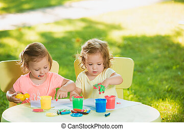Two-year old girls painting with poster paintings together...