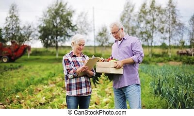 senior couple with box of vegetables on farm - farming,...