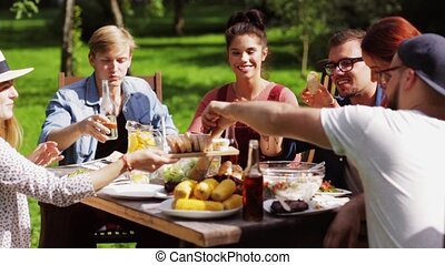 happy friends having dinner at summer garden party