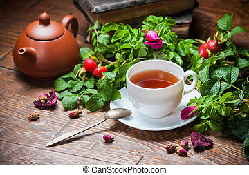 Healthy tea with a dogrose on wooden table