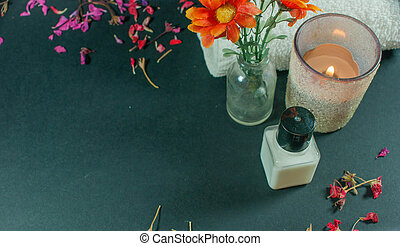 Bottle of body lotion with flowers, petal flowers and towels - black background