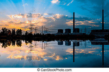 Coal-fired power plant at sunset and reflection in water. -...