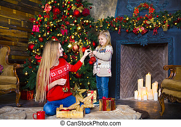 Child girl with mother decorating Christmas tree indoors