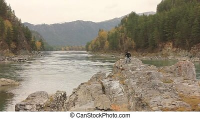 mountain river flowing between rocks with pine trees. traveler standing on a big rock by the river