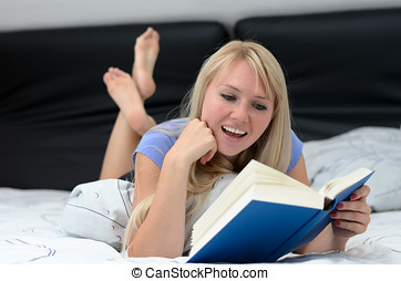 Young woman smiling as she reads a book