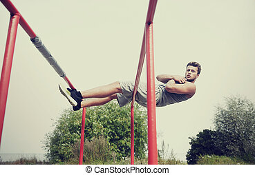 young man doing sit up on parallel bars outdoors - fitness,...