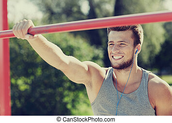 happy young man with earphones and horizontal bar - fitness,...