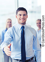 smiling businessman making handshake in office