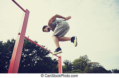 young man jumping on horizontal bar outdoors - fitness,...