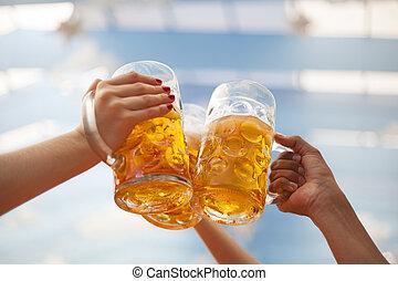 Raised beer mugs toasting at Oktoberfest