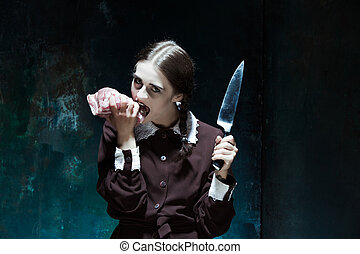 Bloody Halloween theme: crazy girl with a knife and raw meat