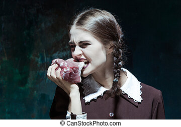 Bloody Halloween theme: crazy girl with raw meat - Portrait...