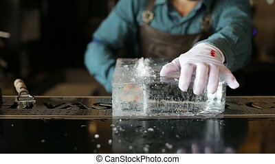 Bartender sawing ice on the bar with a saw.