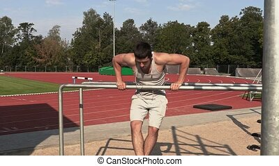 Young athlete do exercises on gymnastic bars