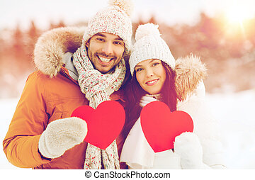 happy couple with red hearts over winter landscape - people,...