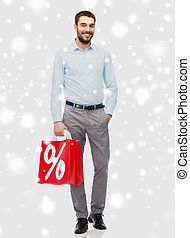 smiling man with red shopping bag over snow - people, sale,...