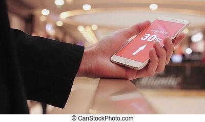 Male hand holds smartphone, discounts on screen white text...