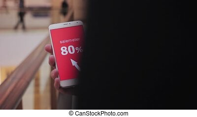 Male hand holds smartphone, discounts on screen white text red background. Shopping mall