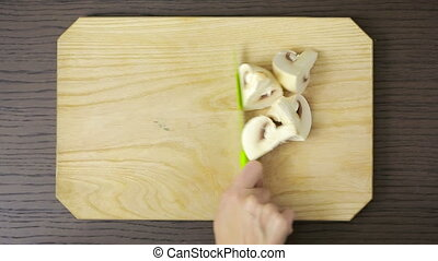 woman cutting a mushrooms on a wooden table. champignon. . top view