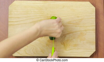 woman cutting cucumber in the kitchen. wooden plank. top view