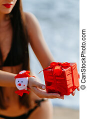 Christmas gift in hands on the beach - santa girl in bikini...
