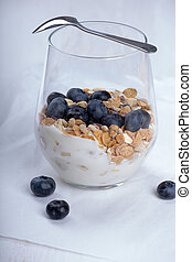 Dietetic breakfast - yoghurt with muesli and huckleberries.