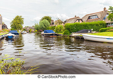 Small river in front of Dutch villa's with boats