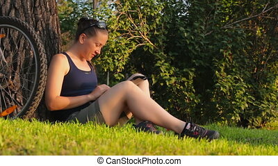Young woman sitting on a green gras - Young woman student...