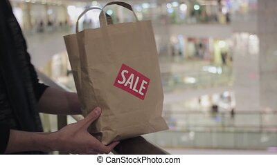 Male hands puts brown paper bag with red SALE sticker on it...
