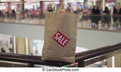 Brown paper bag with red sale sticker on it on handrail in shopping mall