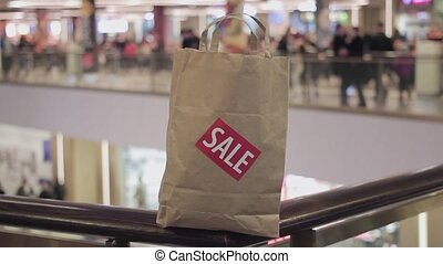 Brown paper bag with red sale sticker on it on handrail in...