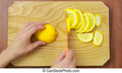 woman cuts lemon on a wooden board. view from above. top view