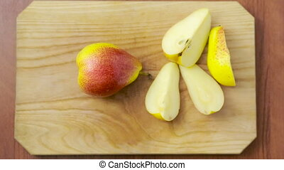 woman cuts a pear on a wooden board. top view - woman cuts a...