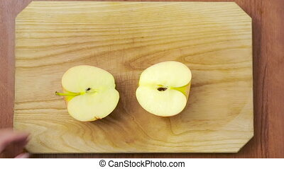 woman cuts an apple on a wooden board cooking food top view...