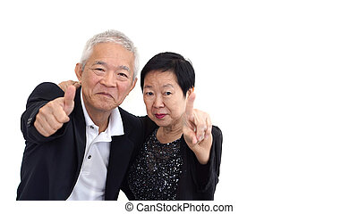 Asian senior couple in business attire showing hand gesture...