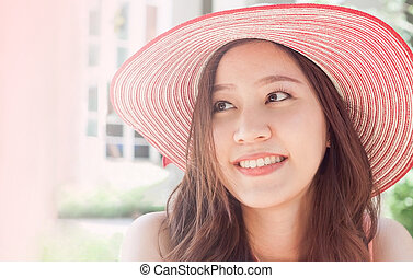 woman wearing pink straw hat with expression of surprise -...