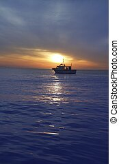 sunset sunrise with fishing boat in horizon blue...