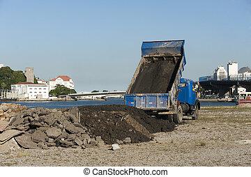 Truck of dump-cart unloading land in an embankment