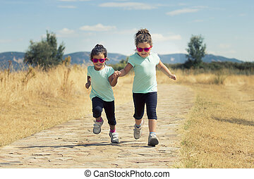 Lovely twins jumping along path in countryside - Portrait of...