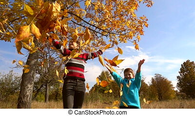Two kids throwing up the autumn leaves, slow motion