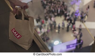 Man puts brown bags with sale sticker on it on floor in mall...