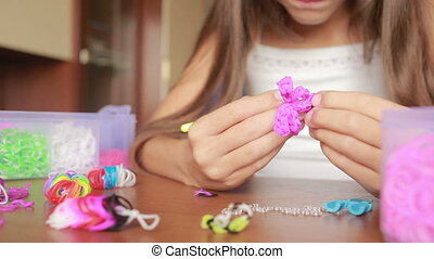 little girl weave wristband of rubber bands Colored rubber...