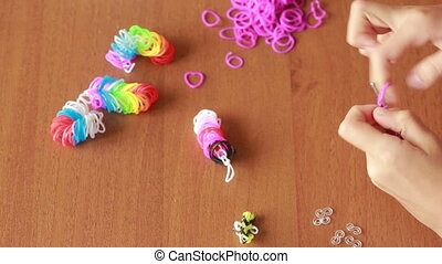 little girl weave wristband of rubber bands. Colored rubber...