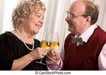 Cheers - Portrait of senior couple celebrating their golden...
