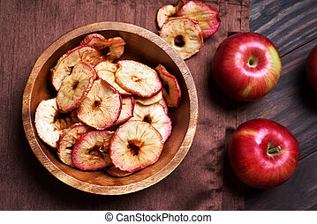 Dehydrated apples chips in wooden bowl, top view