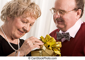 Surprise - Image of aged woman opening giftbox with her...